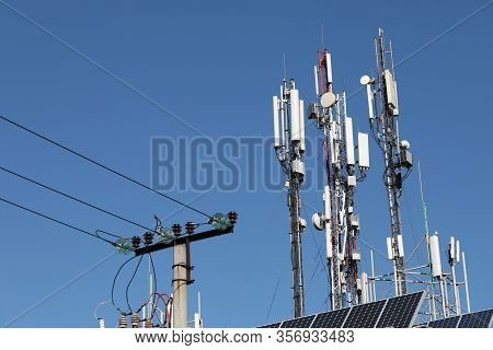 Mobile Towers On Blue Sky Background. Many Communication Equipment.