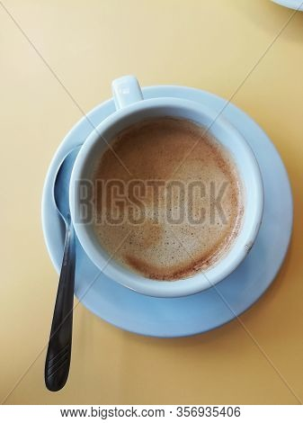 A Simple White Cup Of Cappuccino With The Spoon Aside, On A Table With A Yellow Hue Seen From Above