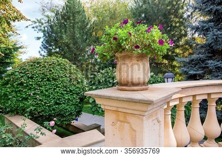 A Beige Stone Flowerpot With Blooming Flowers On The Railing With Balustrades In The Park With Bushe
