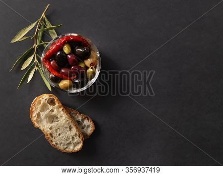Top View Of Bowl With Different Types Of Olives, Chili Pepper, Ciabatta Bread And Olive Twig On Dark