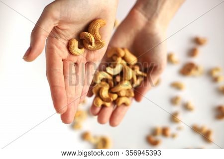 Nuts In The Palms. Pour Nuts From One Palm To Another. Cashew Nuts Sprinkled On A White Background.