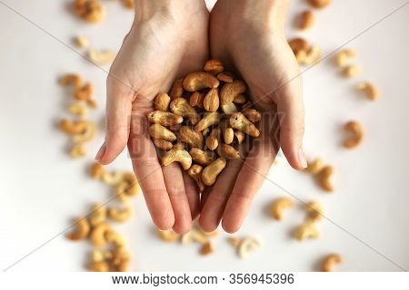 Nuts In The Palms. A Handful Of Nuts In The Palms. Palms With Nuts On A White Background With Spread