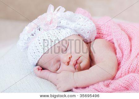 newborn girl sleeps under a knitted pink cape poster