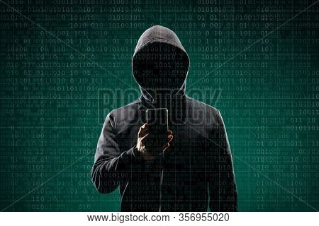 Dangerous Hacker With A Smartphone Gadget Over Digital Background With Binary Code. Obscured Dark Fa