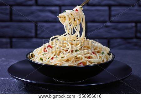 Pasta Aglio, Olio E Peperoncino, Italian Spaghetti With Garlic, Chili And Olive Oil On A Golden Fork