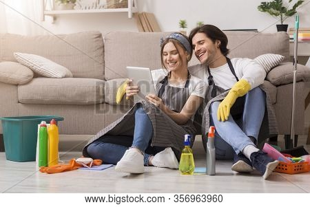 Online Shopping For New Home. Smiling Couple Relaxing With Digital Tablet After Spring-cleaning Apar