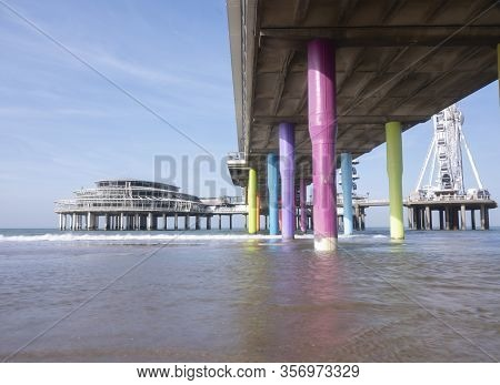 Rainbow Colored Stone Poles Under The Pier Of Scheveningen Beach The Netherlands With Sand And Waves