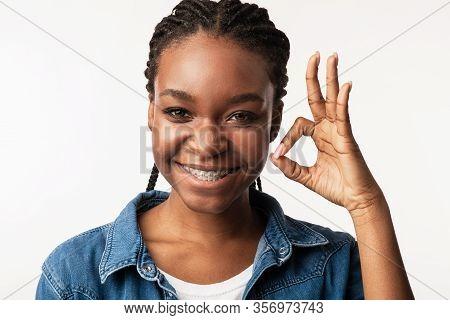 Ok. Black Girl With Braces Gesturing Okay Sign Smiling To Camera Posing In Studio Over White Backgro