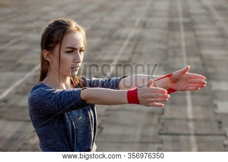 Young Slim Woman In Sportswear Doing Squats Exercise With Rubber Band On A Black Coated Stadium Trac