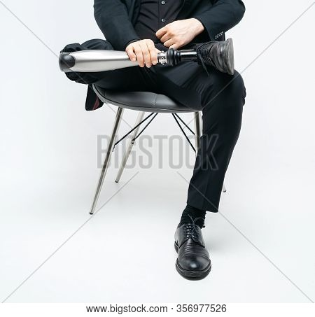 Cropped View Of Disabled Young Man With Prosthetic Leg Sitting On A Chair In Studio, Artificial Limb