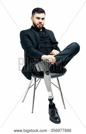 Disabled Young Man With Prosthetic Leg, Artificial Limb Concept. Sitting On A Chair, Isolated On Whi