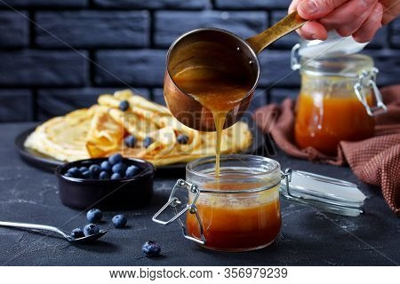 Woman Is Pouring Freshly Cooked Homemade Buttermilk Syrup From Copper Saucepan To A Glass Jar On A C