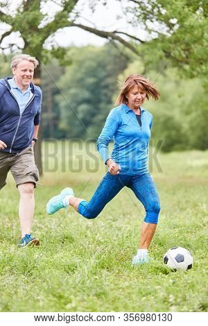 Senior woman playing football with friends in the park as a senior sport