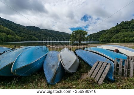 Old Wooden Fishing Boats Lying Overturned On A Grass. Fishing Boats On A Shore With Mountain Lake La