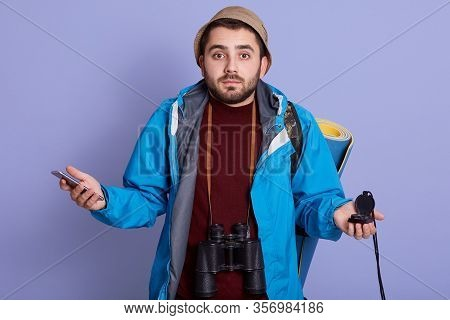 Lost Traveler Spreading His Hands Sides, Posing Isolated Over Lilac Background, Wearing Blue Jacket,