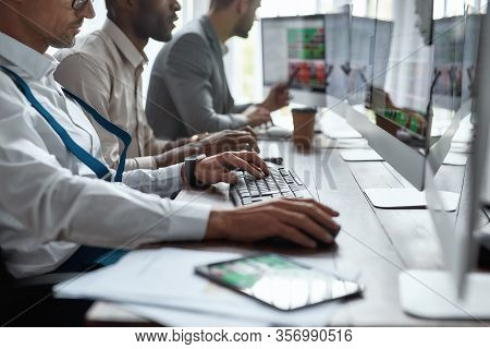 Three Businessmen Sitting At Desktop Front Pc Computers With Financial Graph And Statistics On Monit