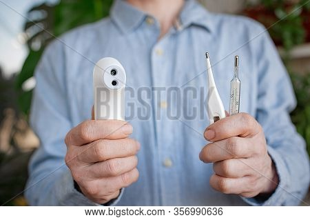 Person Hold Various Thermometers. Mercury , Digital And Non-contact Thermometers. People And Healthc