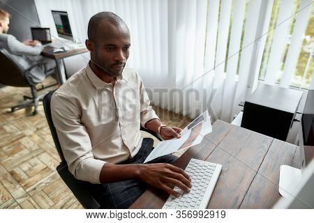 High-angle View Of Young Trader Sitting By Desk And Looking Seriously At Analytical Reports While Wo