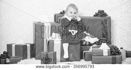 Gifts For Child First Christmas. Little Baby Girl Play Near Pile Of Gift Boxes. Celebrate First Chri
