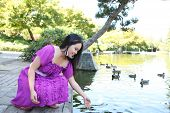 A pretty asian woman playing with fish in pond poster