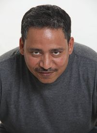 An Indian Man In A Studio Against A White Background Looking Up
