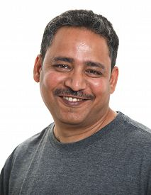 A Smiling Indian Man In A Studio Against A White Background