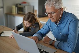 Father and school-girl working form home, telework and e-learning