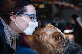 Woman With Mask Kissing Dog. Woman Protecting From Virus. Virus. Living With Coronavirus. Coronaviru