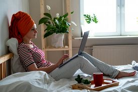Woman With Orange Towel On Head Is Working Office Work Remotely From Home On Bed. Using Computer. Di