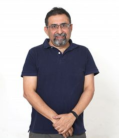 A Smiling Indian Man With A Goatee In A Studio Against A White Background. Wearing Spectacles And Lo