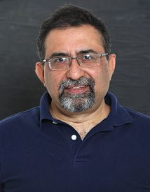 A Smiling Indian Man With A Goatee In A Studio Against A Dark Background. Wearing Spectacles And Loo