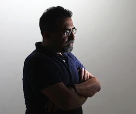 A Indian Man With A Goatee In A Studio Against A White Background. Wearing Spectacles And Looking Aw