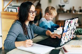 Concept Of Work From Home And Home Family Education. Mom And Son Are Sitting At The Desk. Business W