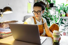 Young Female Gardener In Glasses Using Laptop, Communicates On Internet With Customer In Home Garden