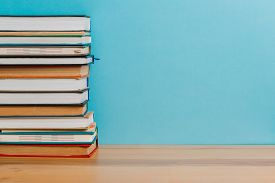 A Simple Composition Of Many Hardback Books, Raw Books On A Wooden Table And A Bright Blue Backgroun