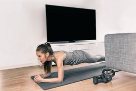Fitness workout at home indoors. Asian girl doing plank exercises to exercise core watching tv videos of fit class. Young woman training muscles in front of the TV without going to the gym.