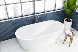 Top View Of Comfortable Bathtub Standing In Panoramic Bathroom With Blue Tiled Walls, Concrete Floor