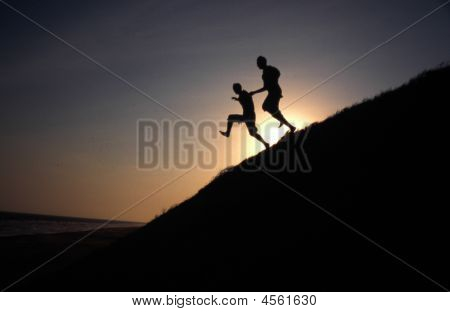 Silhouette Of Two People Running Down A Hill At Sunset