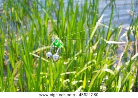 Fishing bite alarm bell in readinesson blurred green vegetation and river poster