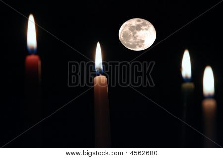 Full Moon Behind Lit Candles