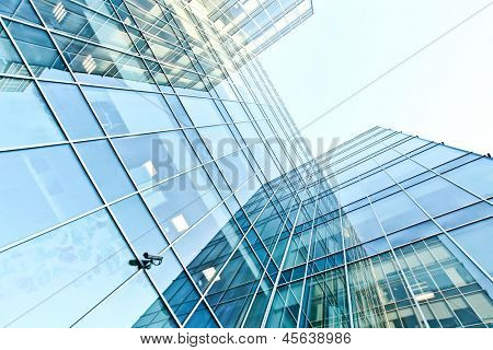 Perspective and underside angle view to textured background of modern glass building skyscrapers with mirrored reverberation over blue cloudless sky poster