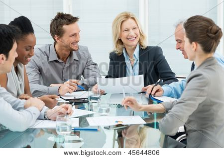Group Of Happy Coworkers Discussing In Conference Room