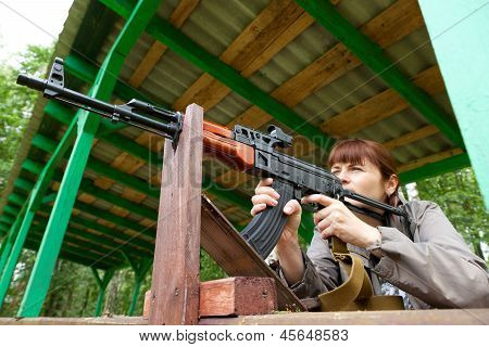 Young Woman Aiming At A Target And Shooting An Automatic Rifle For Strikeball. Focus On The Rifle.