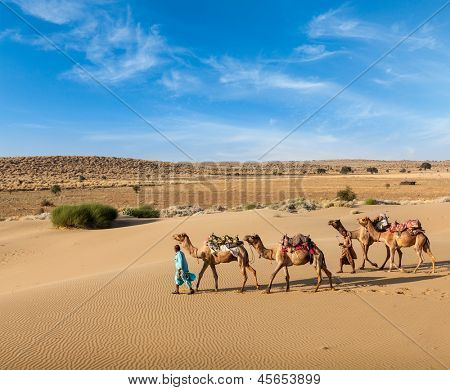 Rajasthan travel background - two Indian cameleers (camel drivers) with camels in dunes of Thar desert. Jaisalmer, Rajasthan, India