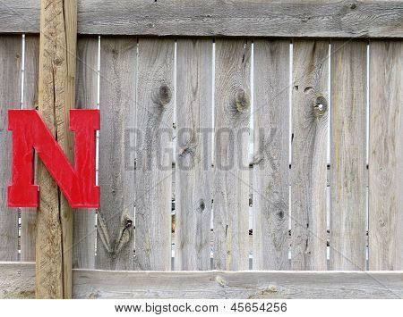 Red Letter N on Gray Wood Fence