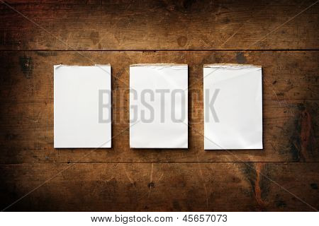 Three real-life condition memo pads on an old grungy wooden surface. For inserting your  messages. poster