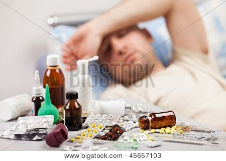 Adult man patient with high temperature lying down bed for cold and flu illness relief