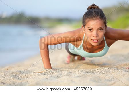 Push-ups fitness woman doing pushups outside on beach. Fit female sport model girl training outdoors. Mixed race Asian Caucasian athlete in her 20s.