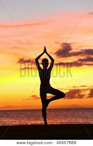 Yoga woman training in sunset in tree pose meditating outdoors by beach ocean sea. Female yoga instructor working out training in serene ocean landscape. Silhouette of woman model against sun.