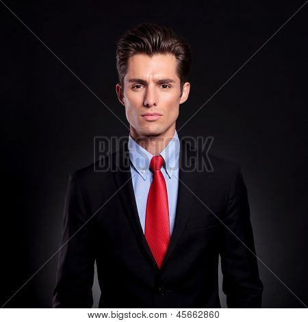 portrait of a young business man standing against a black background and looking at the camera with a straight face